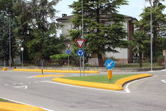 Roundabout with yellow curb and green grass in summer Stock Image