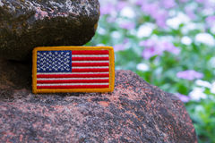 Rounded American flag patch. Stick on Special force Modern combat helmet with purple flower background Stock Photos