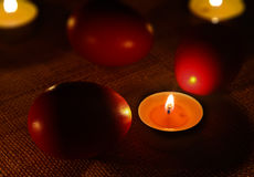 Rounded candle placed between three red eggs Stock Photos
