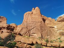 Rounded desert mountain peak at Arches National Park. Surrounded by brush, with blue sky in the background Royalty Free Stock Photos