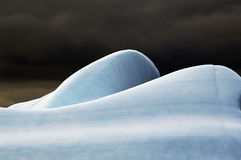 Rounded iceberg. The rounded top of an Antarctic iceberg in front of a dark sky royalty free stock image