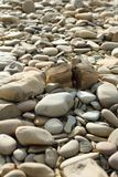 Rounded pebbles on the beach. Beige pebbles on the beach and stone split in half royalty free stock photos