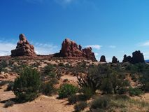 Rounded rock formations at Arches National Park. With plants and sand in the foreground Royalty Free Stock Photo