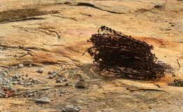 Rounded rusty pin wire on the hill rock. Royalty Free Stock Images