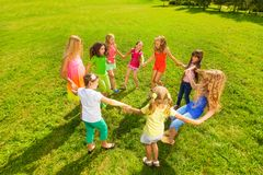 Roundelay in the park. Many happy girls play roundelay and dance and stand in circle in the park on the green grass on sunny summer day Royalty Free Stock Image