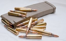.223 rounds and a loaded magazine. Several .223 caliber rounds and a loaded magazine on a white backgroundn Royalty Free Stock Photography