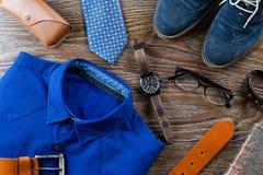 Roupa à moda do homem e configuração lisa dos acessórios em cores azuis e marrons em um fundo de madeira Imagem de Stock
