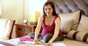 Roupa bonito do bebê da dobradura da mulher gravida video estoque
