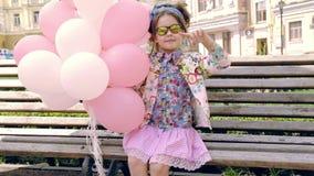 A roupa bonito pequena do estilo da forma do cabelo escuro da menina veste-se para a posse da criança cor-de-rosa e os balões bra filme