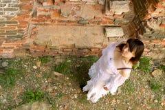 Roupa branca em uma moça no fundo da parede de tijolo Fotos de Stock Royalty Free