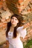 Roupa branca em uma moça no fundo da parede de tijolo Foto de Stock