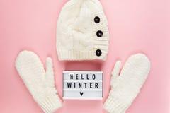Roupa branca morna, acolhedor do inverno, chapéu, mitenes, lightbox no fundo cor-de-rosa pastel Configuração do plano do conceito foto de stock