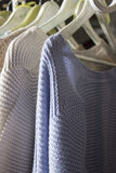 Roupa caseiro feita malha das cores diferentes que penduram no stor Fotografia de Stock Royalty Free