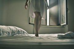 A roupa colocou oLegs de uma mulher vestida na posição branca em uma cama branca foto de stock