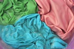 Roupa colorida em um close-up da bacia de lavagem, fundo fotos de stock