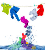 A roupa colorida voa fora da água, isolada no branco foto de stock