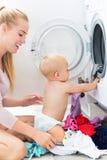 Roupa da carga da mãe e do bebê na máquina de lavar Imagem de Stock