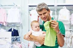Roupa da compra do homem e do bebê Fotografia de Stock
