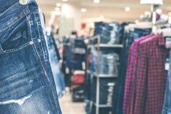 Roupa das calças de brim que pendura na loja foto de stock