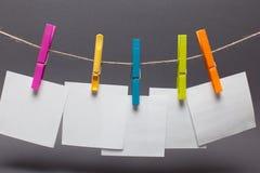 Roupa das cores e etiquetas de papel para o close up das notas Fotos de Stock