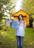 A roupa das crianças de suspensão exteriores da mulher gravida bonita Imagem de Stock