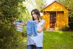 A roupa das crianças de suspensão exteriores da mulher gravida bonita Fotos de Stock Royalty Free
