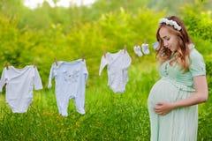 A roupa das crianças de suspensão exteriores da mulher gravida bonita Grande tempo Foto de Stock Royalty Free