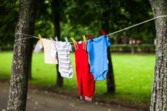 A roupa das crianças em uma corda imagens de stock royalty free