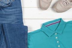 Roupa das mulheres ajustada e acessórios em um fundo de madeira rústico Esportes t-shirt e sapatilhas em cores brilhantes Vista s Fotos de Stock Royalty Free
