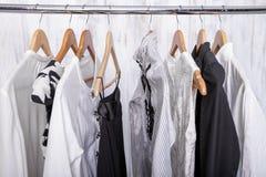 A roupa das mulheres preto e branco em ganchos na cremalheira no sto da forma Imagens de Stock Royalty Free