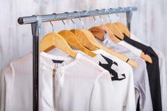 A roupa das mulheres preto e branco em ganchos na cremalheira no sto da forma Fotos de Stock Royalty Free