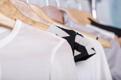 A roupa das mulheres preto e branco em ganchos na cremalheira no sto da forma Foto de Stock
