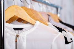 A roupa das mulheres preto e branco em ganchos na cremalheira no sto da forma Fotografia de Stock