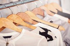 A roupa das mulheres preto e branco em ganchos na cremalheira no sto da forma Fotos de Stock