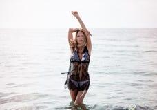 Roupa de banho branco vestindo da mulher loura bonita nova da forma e estada preta do cabo da praia do laço no mar foto de stock royalty free