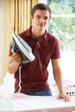 Roupa de Fed Up Teenage Boy Ironing fotografia de stock