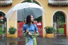 Roupa de senhora vietnamiano Ao dai que guarda o guarda-chuva na chuva imagem de stock