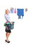 Roupa de suspensão da mulher nova na linha de roupa Imagens de Stock