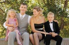 A roupa desgastando do feriado da família senta-se e sorri-se Fotos de Stock
