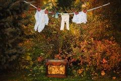 A roupa do bebê é de suspensão e de secagem em uma corda i exterior Fotos de Stock Royalty Free