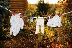 A roupa do bebê está pendurando e dryingon uma corda exterior dentro Imagens de Stock