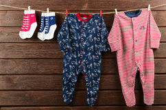 Roupa do bebê & x28; sleepsuits e socks& x29; suspensão no clothesli fotografia de stock