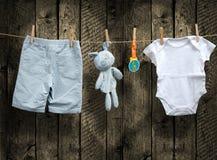 Roupa do bebê e coelho enchido em uma corda Imagens de Stock