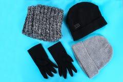 Roupa do inverno e do outono, chapéus, scarves, luvas em um fundo pastel azul fotos de stock royalty free