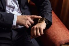 Roupa do pulso de disparo do homem de negócios, homem de negócios que verifica o tempo em seus wris Foto de Stock Royalty Free