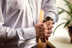 Roupa do pulso de disparo do homem de negócios, homem de negócios que verifica o tempo em seus wris Imagens de Stock