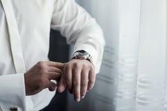 Roupa do pulso de disparo do homem de negócios, homem de negócios que verifica o tempo em seus wris Fotos de Stock