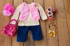 A roupa e os acessórios das crianças: veste, calças de brim, revestimento, sapatas, chapéu e bolsa Fotos de Stock