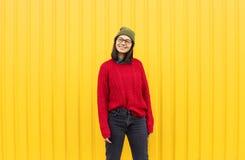 Roupa elegante da menina im de Millenial que tem uma boa estadia, fazendo as caras engraçadas perto da parede urbana amarela bril fotos de stock royalty free