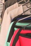 Roupa em ganchos em uma loja Imagens de Stock